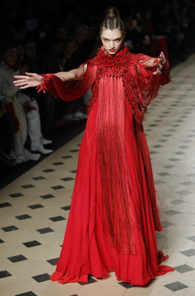 Julien Fournié défilé Haute Couture, un mannequin habillé d'une robe rouge déploie ses bras et offre un regard mystérieux aux spectateurs.